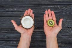 Kiwi och kokosnöt i händer Arkivfoto
