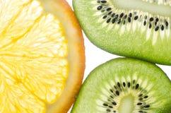 Kiwi, orange in einem Schnittweißhintergrund Lizenzfreie Stockfotos
