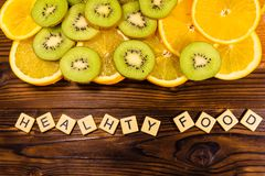 Kiwi and orange fruits on wooden table. Top view. Healthy food i. Kiwi and orange fruits on a wooden table. Top view. Healthy food inscription Stock Photography