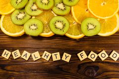 Kiwi and orange fruits on wooden table. Top view. Healthy food i. Kiwi and orange fruits on a wooden table. Top view. Healthy food inscription Royalty Free Stock Photography