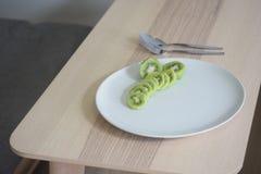 Kiwi på den vita maträtten royaltyfri foto