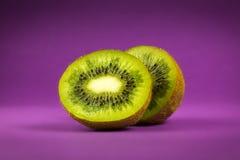 Kiwi på purpurfärgad bakgrund royaltyfri fotografi