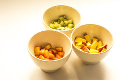 Kiwi, peach and plum in white bowls. Ideal for wallpapers. Could be useful in presentations, web and printing design Stock Images