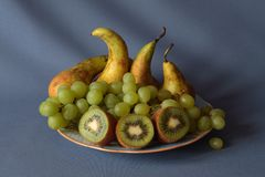 Kiwi, pears and grapes on a plate. Still life fruit and berry. One bunch of green grapes, three cut kiwis and four pears on a plate. In the foreground kiwi, then royalty free stock photos