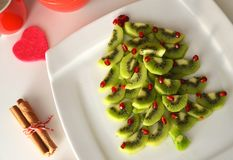Kiwi and pomegranate Christmas tree New Year background. Healthy dessert idea for kids party. Kiwi and pomegranate Christmas tree New Year. Healthy dessert idea royalty free stock image
