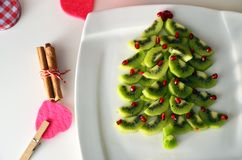 Kiwi and pomegranate Christmas tree New Year background. Healthy dessert idea for kids party. Kiwi and pomegranate Christmas tree New Year. Healthy dessert idea stock photography