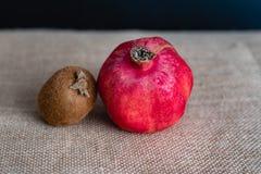 Kiwi and pomegranate on wooden background stock photo