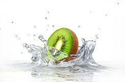 Kiwi que salpica en el agua clara. imagenes de archivo