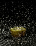 Kiwi in the rain. A half of a kiwi lying in the rain Royalty Free Stock Photos
