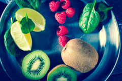 Kiwi, raspberries, lime and baby spinach. Kiwi fruits, raspberry, lime and baby spinach leaves lying on a silver metal plate top view Stock Photography