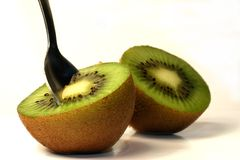 Kiwi - ready to eat. A sliced kiwi fruit, isolated on white, complete with spoon ready to eat Royalty Free Stock Image