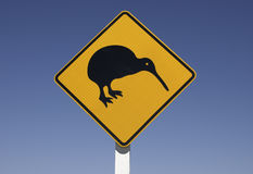 Kiwi on the road. Yellow kiwi traffic sign with blue background royalty free stock photos