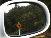 Kiwi road sign reflected in a car mirror. Shot of a kiwi road sign reflected in a car mirror in new zealand stock photos