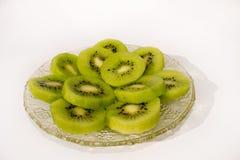 Kiwi sabroso verde jugoso fresco en la placa cristalina con el fondo blanco imágenes de archivo libres de regalías