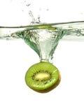 Kiwi-Scheibe, die in Wasser spritzt Stockbild