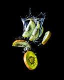Kiwi schneidet das Fallen in die Wassernahaufnahme, Makro, Spritzen, die Blasen, lokalisiert auf Schwarzem Stockbild
