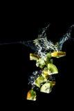 Kiwi schneidet das Fallen in die Wassernahaufnahme, Makro, Spritzen, die Blasen, lokalisiert auf Schwarzem Lizenzfreies Stockfoto