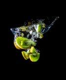 Kiwi schneidet das Fallen in die Wassernahaufnahme, Makro, Spritzen, die Blasen, lokalisiert auf Schwarzem Stockfotografie