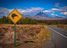 Kiwi sign in NZ landscape. Kiwi warning sign with tongariro volcano in background, New Zealand royalty free stock image