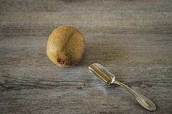 A kiwi with a silver spoon. On a wooden table. Breakfast with fruit Stock Photography
