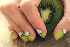 Kiwi art manicure. Kiwi and skin care of a beauty female hands with green and white moon nail art manicure royalty free stock photos