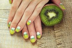 Kiwi art manicure. Kiwi and skin care of a beauty female hands with green and white moon nail art manicure on a sackcloth and wooden background royalty free stock photo