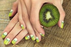 Kiwi art manicure. Kiwi and skin care of a beauty female hands with green and white moon nail art manicure on a sackcloth and wooden background stock image