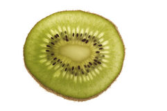 Kiwi Slice. Backlit slice of Kiwi on a white background Royalty Free Stock Images