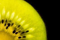 Kiwi slice. Quarter of a kiwi slice isolated on black royalty free stock image