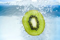 Kiwi slice. In blue water with air bubble royalty free stock photo