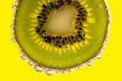 Kiwi slice with bubbles Stock Image