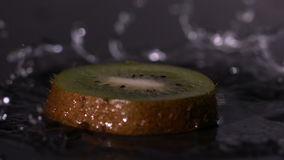 Kiwi slice falling on wet black background stock footage