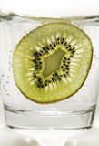Kiwi slice in sparkling water. Kiwi slice in the glass of soda Stock Photo