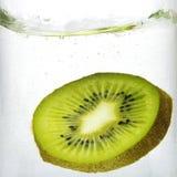 Kiwi slice splash in water. Slice of fresh green kiwi in water splash royalty free stock photo