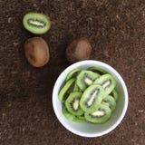 Kiwi. Sliced green kiwis in a white bowl with 3 fruits on side stock photos