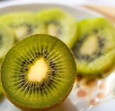 Kiwi sliced in half close up. With green kiwi slices in the background Royalty Free Stock Photos