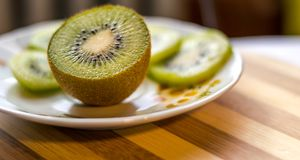 Kiwi sliced in half close up plate level view. Kiwi sliced in half close up with green kiwi slices in the background Stock Photography