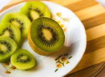 Kiwi sliced in half close up side view. Kiwi sliced in half close up with green kiwi slices in the background Royalty Free Stock Image