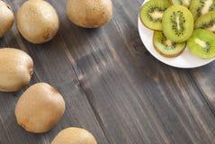Kiwi sliced on plate. Wooden tabnl Royalty Free Stock Photos