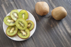 Kiwi sliced on plate. Wooden tabnl Stock Images