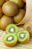 Kiwi sliced and whole fruits, basket Stock Photos