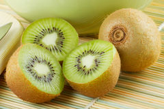Kiwi sliced and whole fruits, green bowl Stock Photography