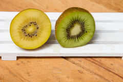 Kiwi sliced. Yellow kiwi and green kiwi fruit isolated. On wooden background Royalty Free Stock Photo