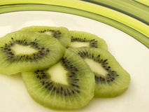 Kiwi slices. On a green rimmed plate royalty free stock photos