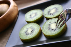 Kiwi slices. Slices of kiwis on a black plate Stock Photos