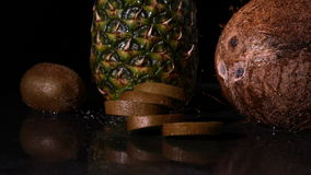 Kiwi slices falling in front of pineapple and coconut stock video footage