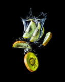 Kiwi slices falling into the water close-up, macro, splash, bubbles, isolated on black Stock Image