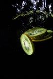 Kiwi slices in water splash. Some kiwi slices splash in water Royalty Free Stock Image