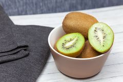 Kiwi slices on a wooden table near a dark cloth, top view stock images
