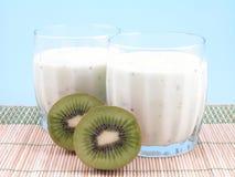 Kiwi smoothie. Tow glasses of kiwi smoothie and some fresh fruits stock photos